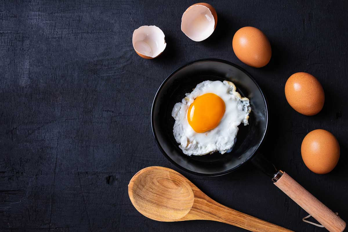 Fried eggs in a frying pan and egg shell for breakfast