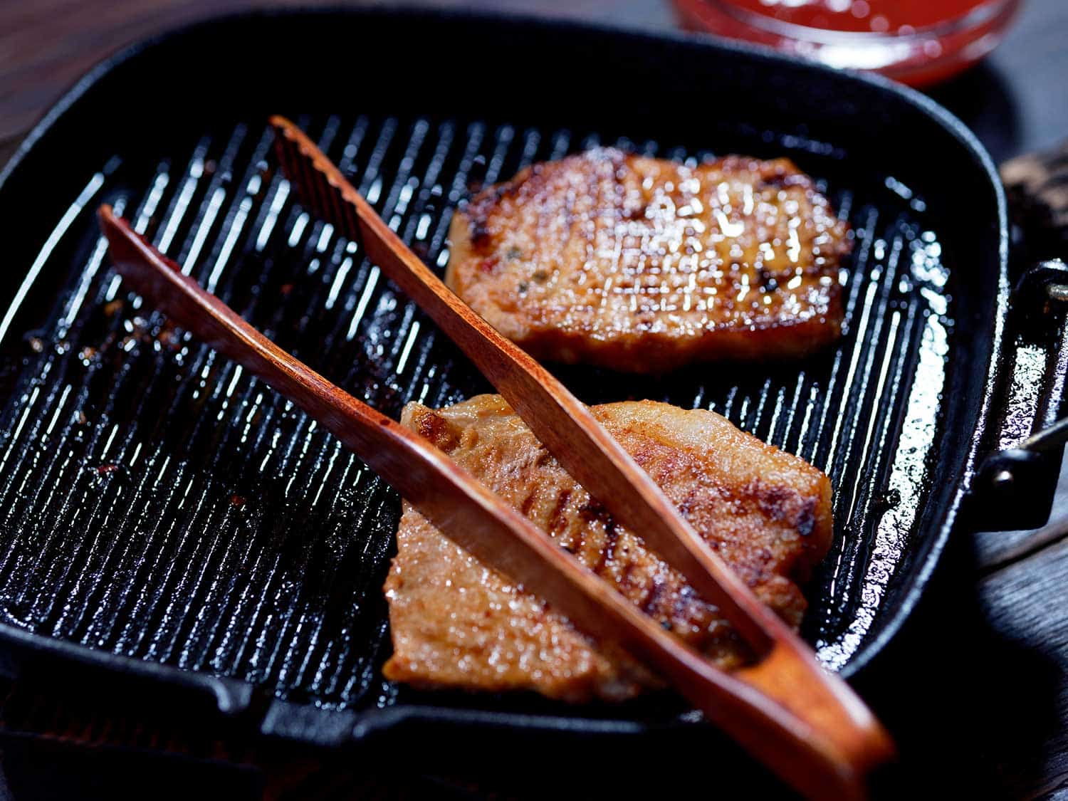 Grilled pork chops in the grill pan on the table