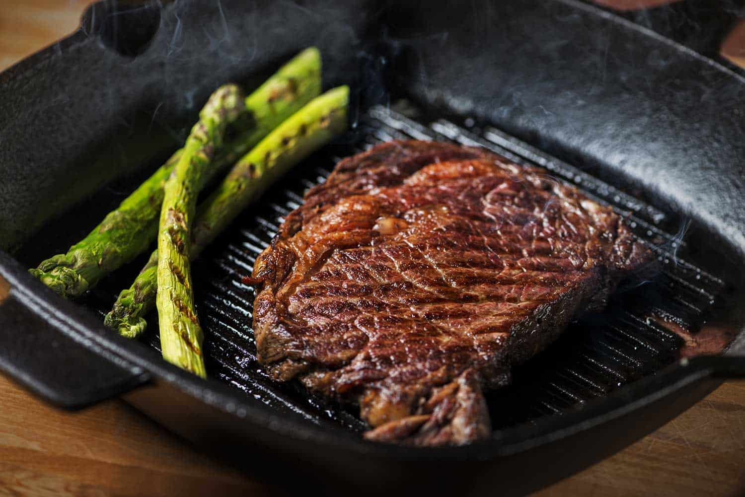 Ribeye steak grilled with asparagus, with visible smoke rising from the hot cast iron pan