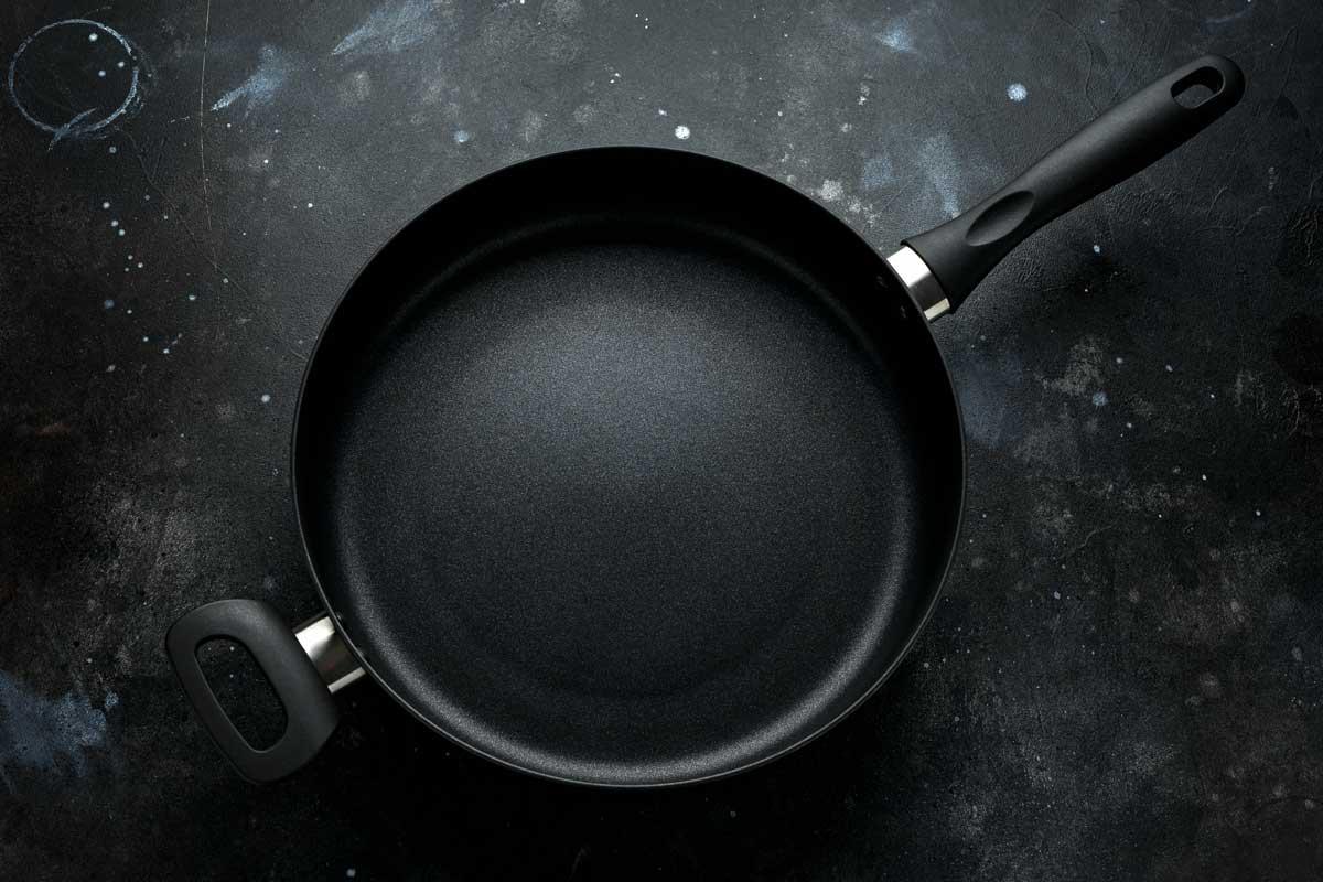 new non-stick aluminium frying pan on dark background.
