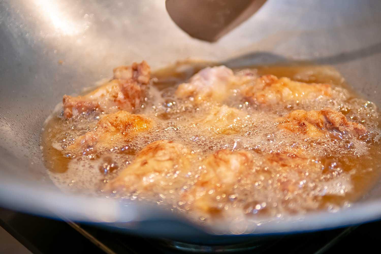 Deep frying chicken drumsticks in a pan