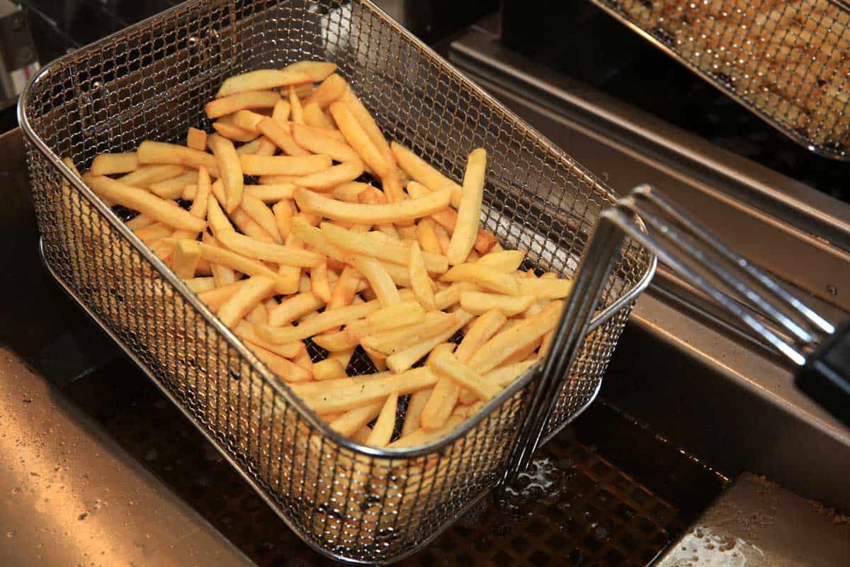 French fries in a fry steel basket deep fryer