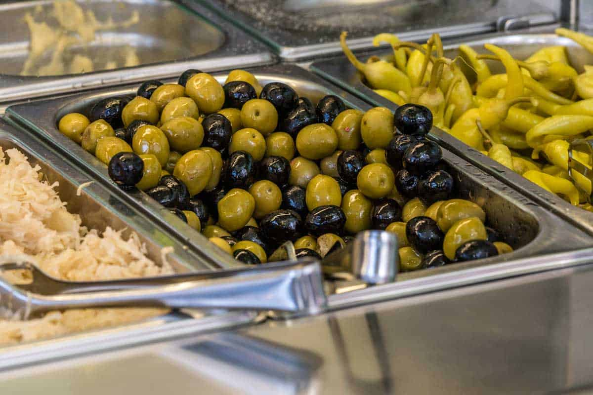 Green peppers, black olives, green olives and cabbage in a bain-marie at a cafeteria, How Long Can You Keep Food In A Bain-Marie?
