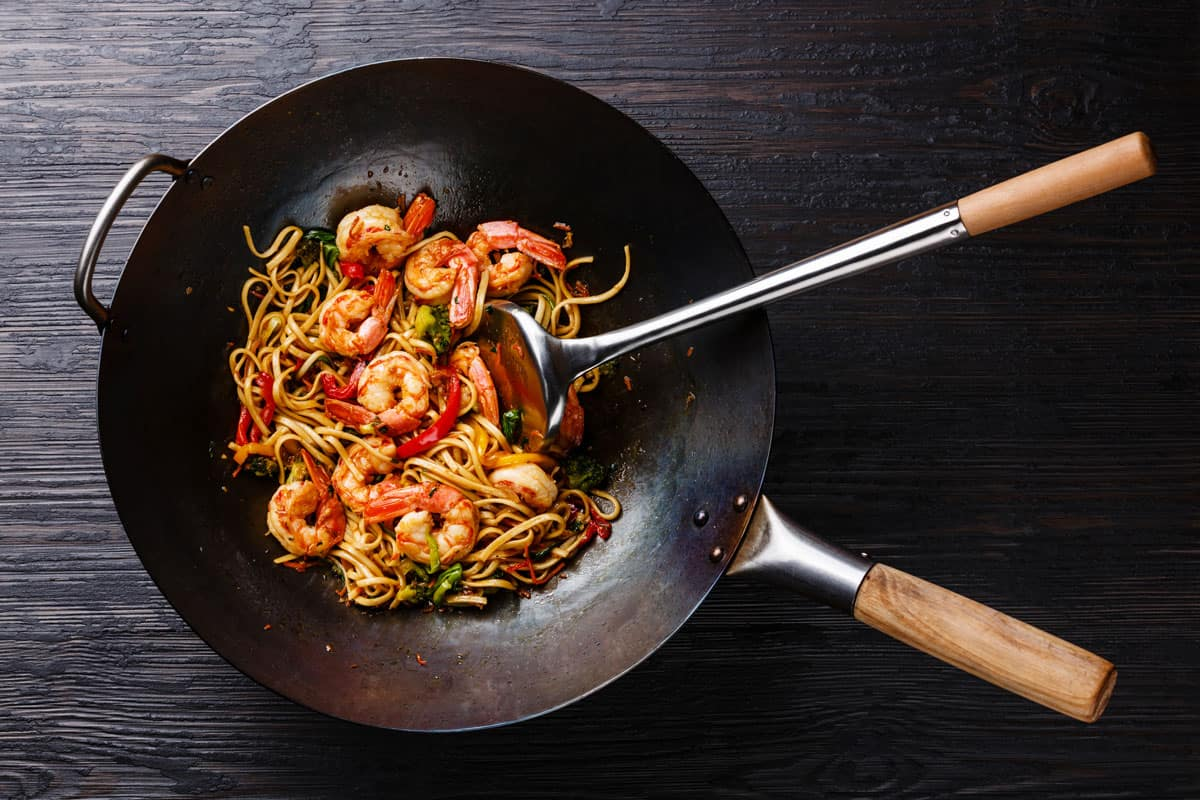 Stir fry udon with shrimps cooked on wok with spatula for mixing, Should A Wok Be Nonstick?