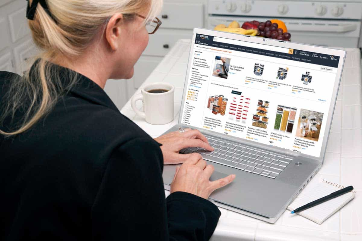 Woman in kitchen checking over her laptop browsing where to buy food containers online, Where To Buy Food Containers