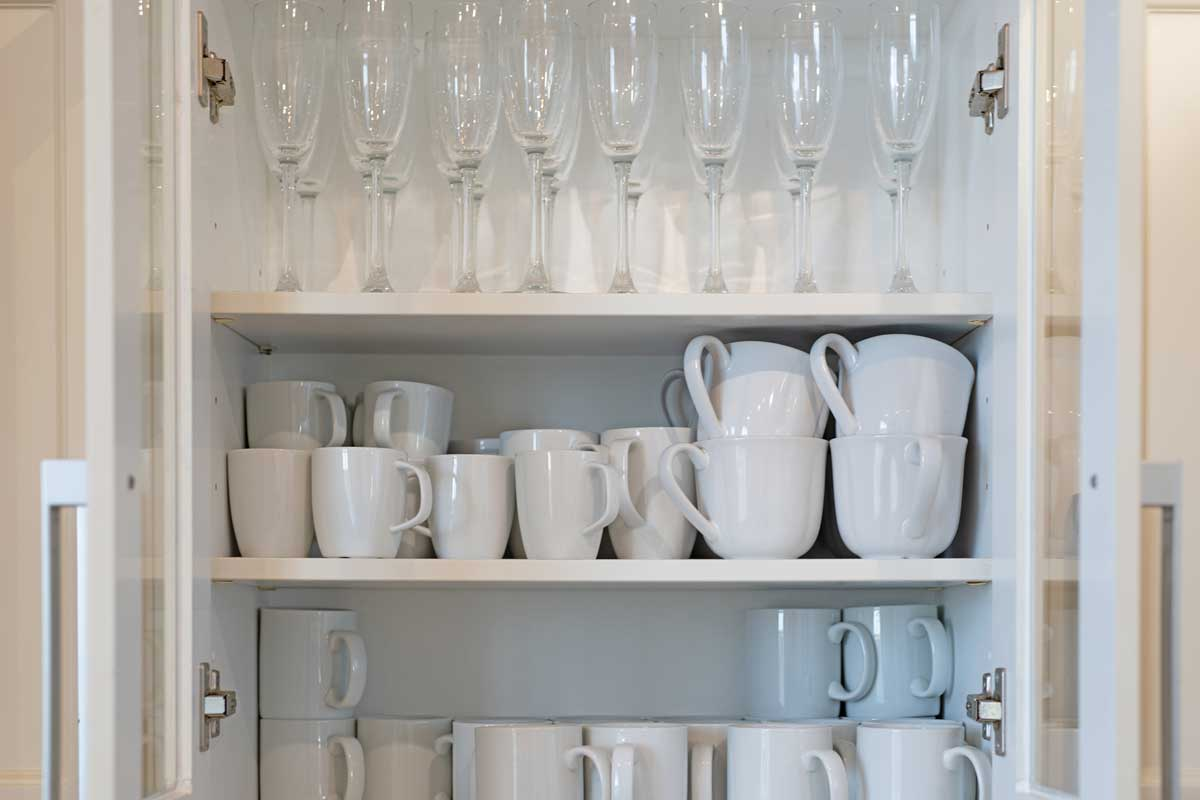 A shelf storage full of white mugs and champagne glasses, How to Store Glasses and Cups in The Kitchen