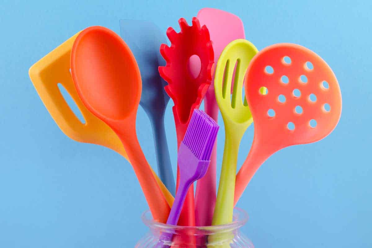 Bright multi colored silicone kitchen utensils on blue background, What Is Better: Nylon Or Silicone Utensils?
