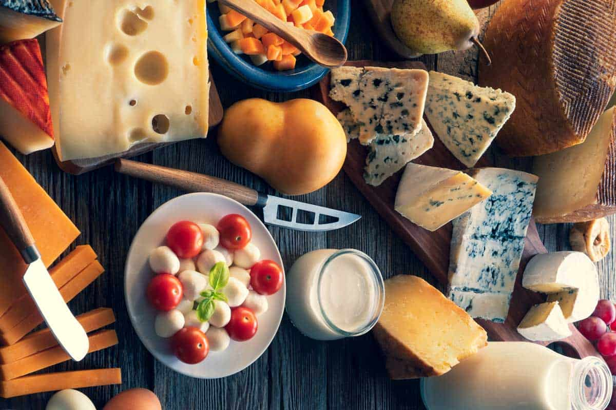 Cheese board with many varied cheeses and dairy products on a table featuring cheese knife, Why is There A Hole in a Cheese Knife?