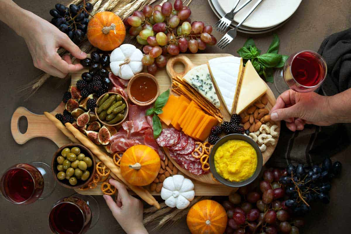 Fantastic italian gifts presented at Fall holidays party table with friends hands picking some fingerfoods from charcuterie board, top down view, 15 Fantastico Italian Cooking Gifts