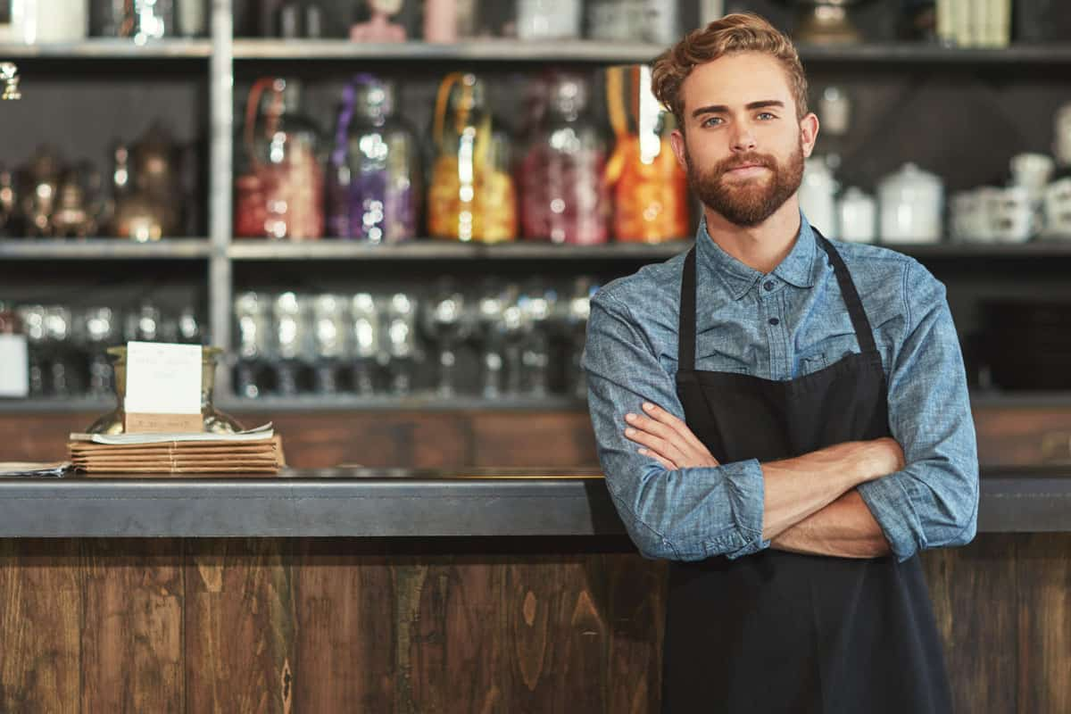 Man with attractive beard wearing black apron as a kitchen gift to him, 27 Awesome Kitchen Gifts for the Man in Your Life
