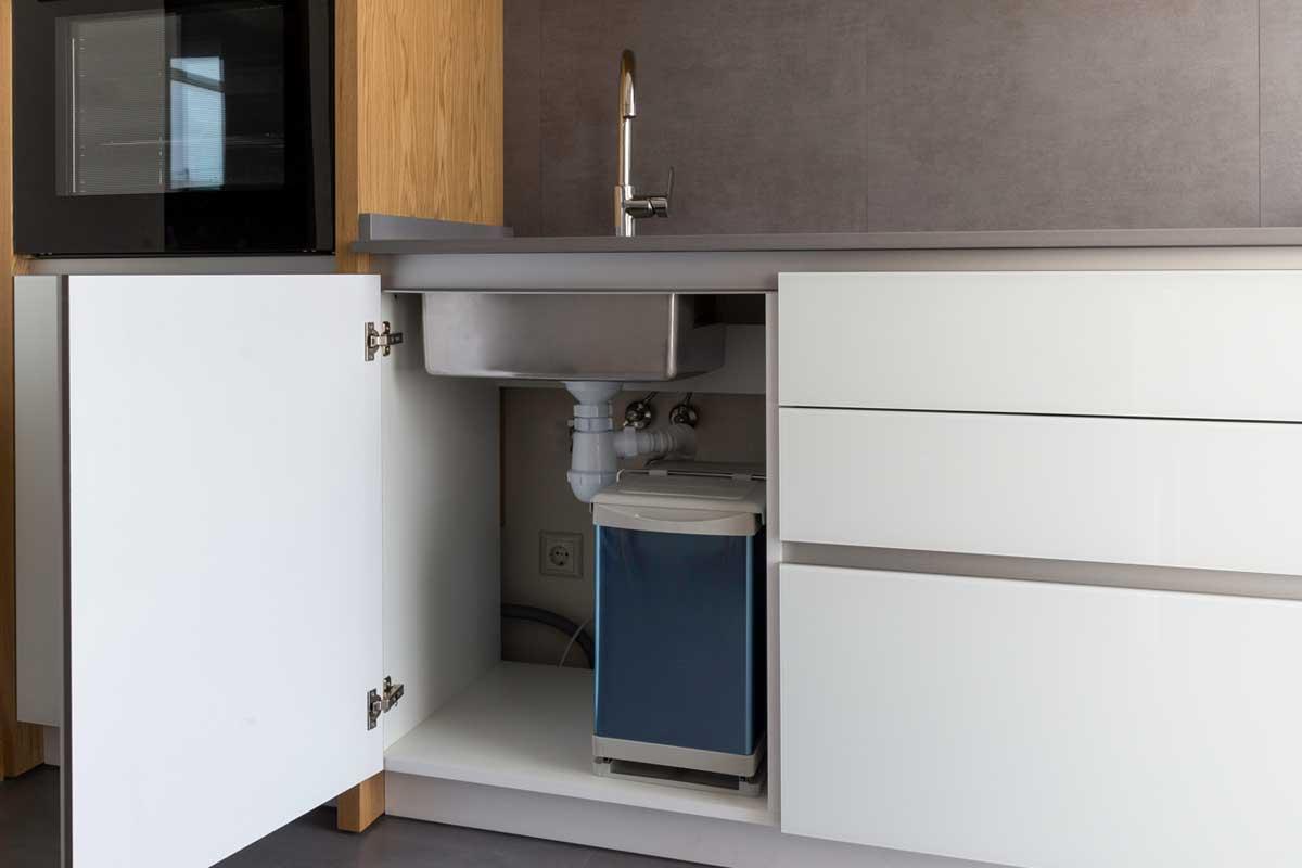 Opened kitchen cabinet with sink and installed garbage bin, 15 Awesome Under-Kitchen-Sink Storage Ideas