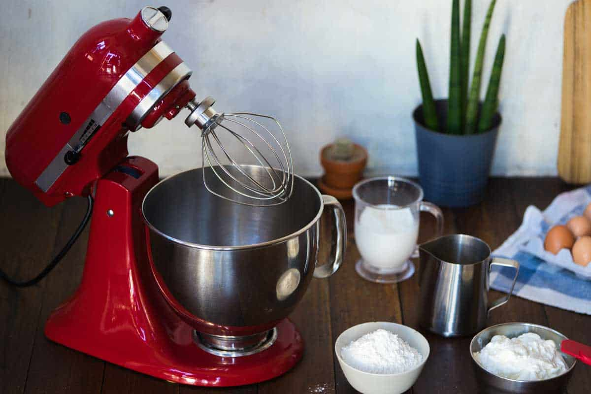 Red standing mixer with ingredients on the wooden table, KitchenAid Accessories For Your Stand Mixer