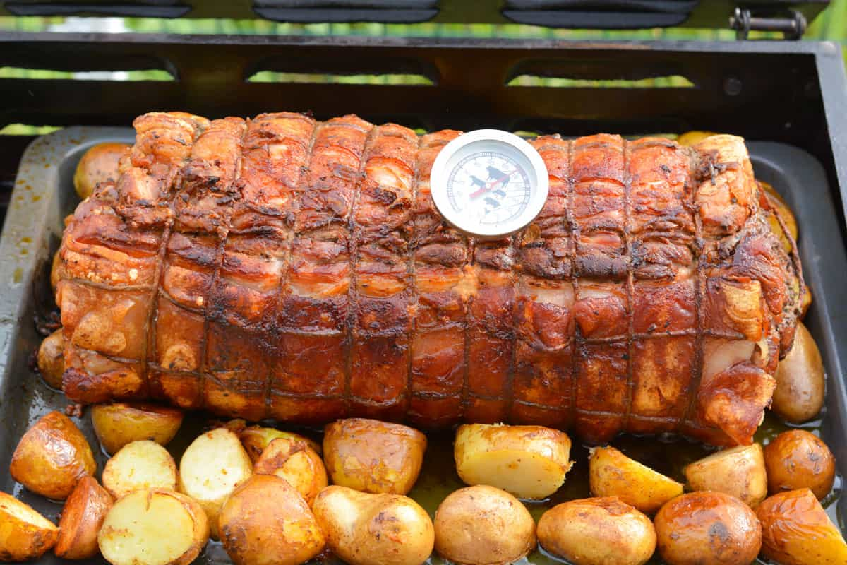 Rolled pork belly meat with potatoes on the side and meat thermometer
