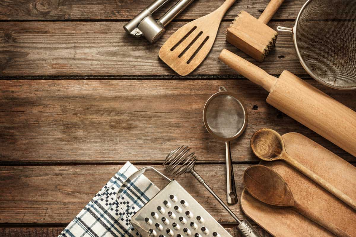 Rural kitchen utensils on vintage planked wood table from above- a perfect gift for cooking lovers, 15+ Kitchen Utensil Gift Sets For Cooking Lovers