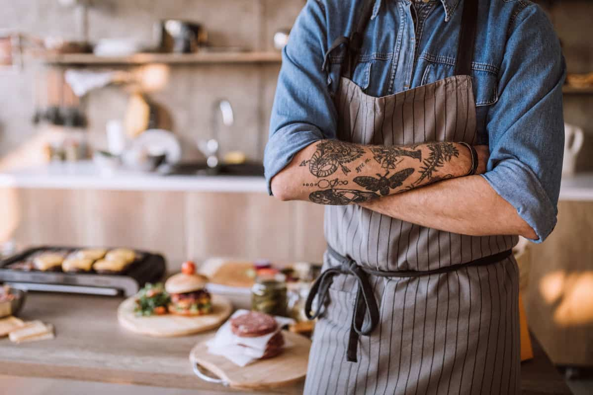 Unknown man wearing fancy apron with arms crossed, 13 Novelty Aprons For Men [Gift Ideas]