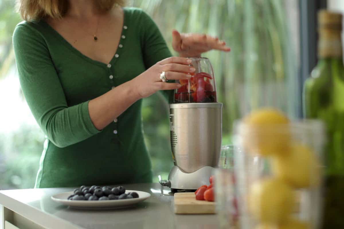 Woman blending many varieties of fruits into her blender, What Can You Use A Nutribullet Blender For?