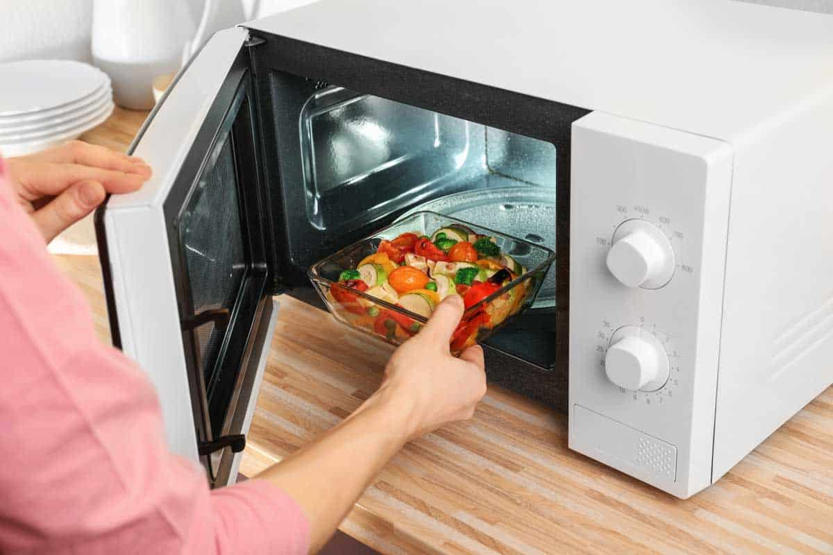 Woman putting bowl with vegetables in microwave oven, closeup