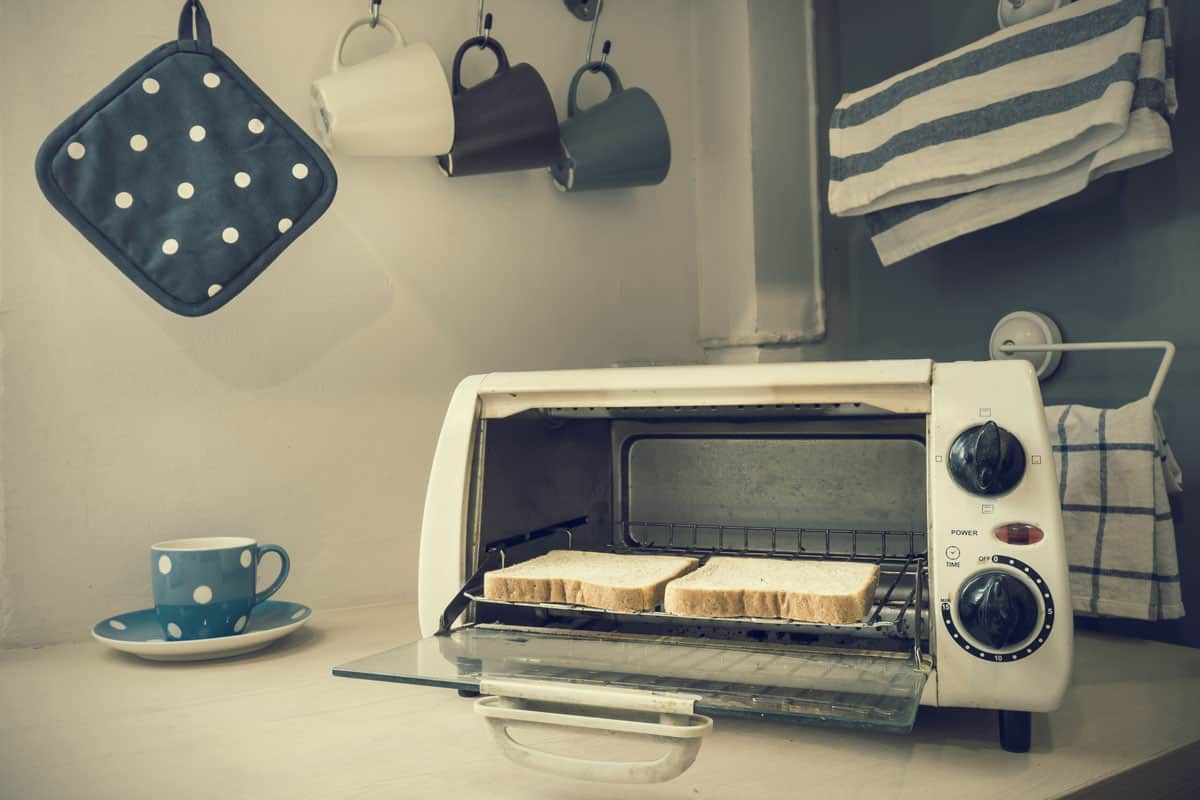 An old oven toaster with two loads of bread inside and hanging cups on the background, Where to Recycle A Toaster Oven?