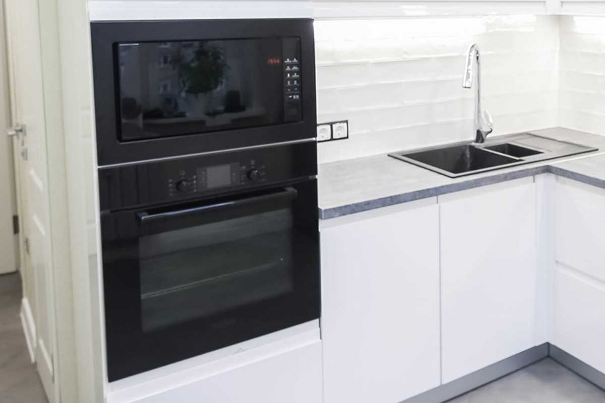 Interior of a modern compact white kitchen with gas stove and wall oven, What is the Best Brand For Wall Ovens? [7 brands reviewed]
