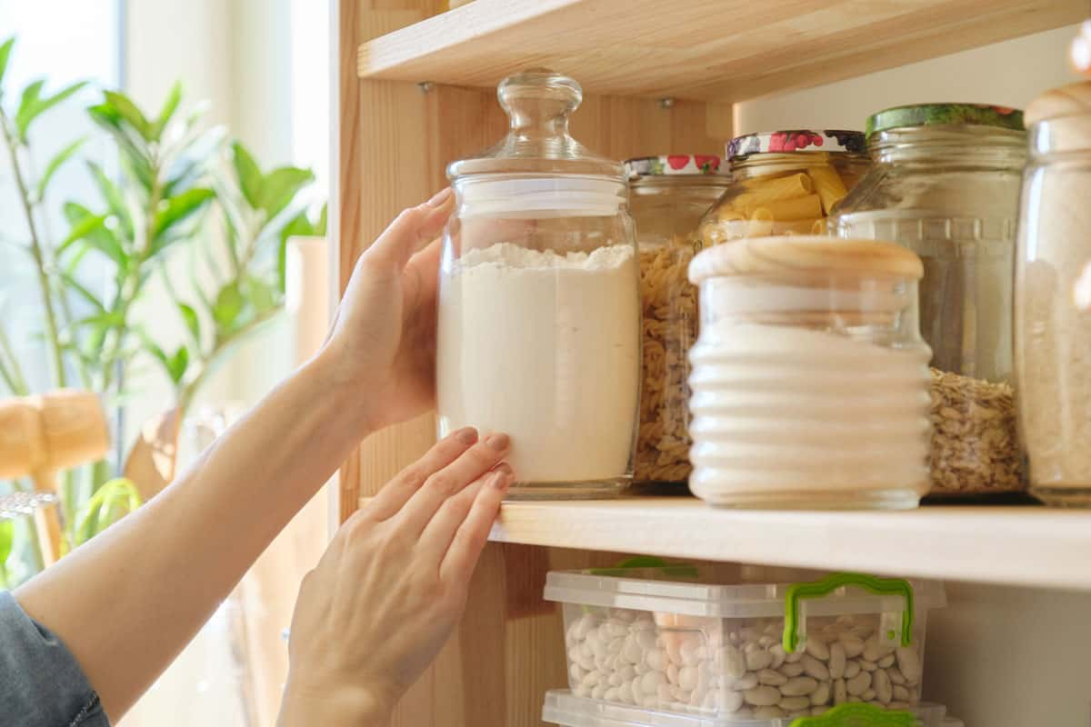 A glass jar with flour inside it properly arranged on a divider, What Is The Best Container To Store Flour? [7 Suggestions]