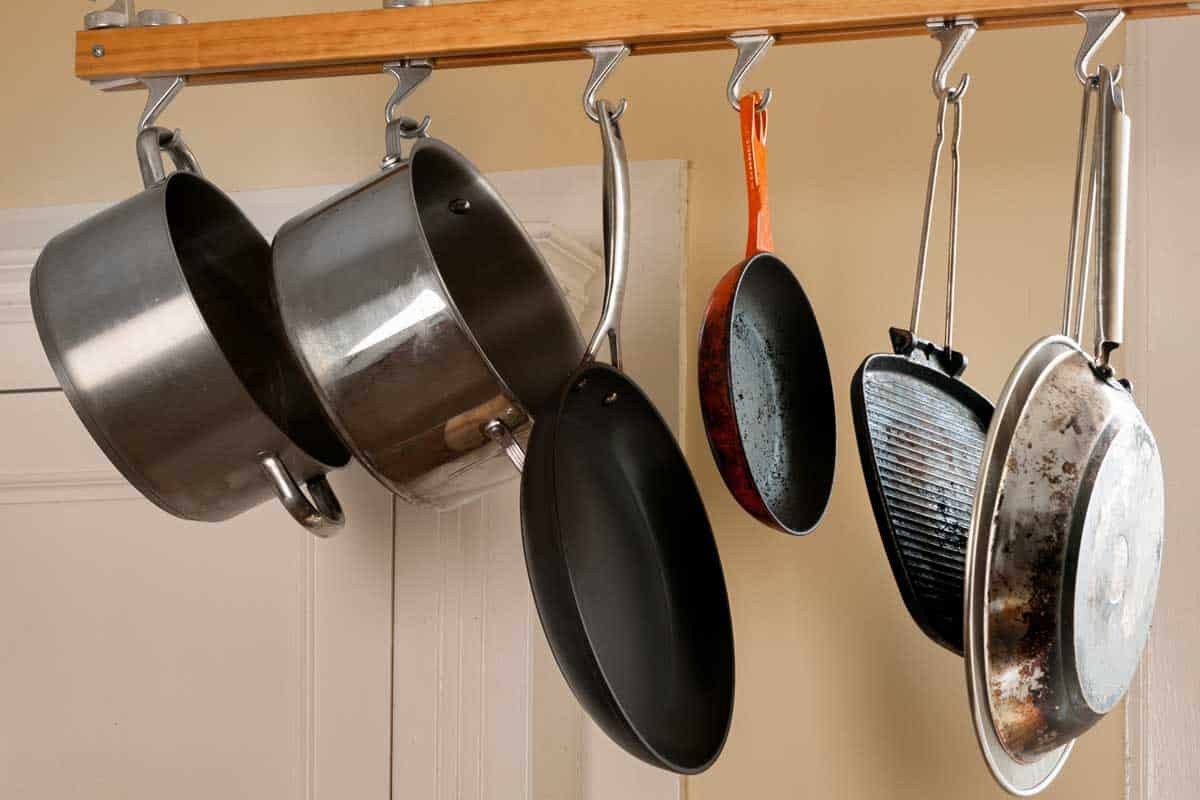 Modern kitchen with a rack of hanging pots and pans, Where Should You Store Heavy Pots? [8 Options Explored]