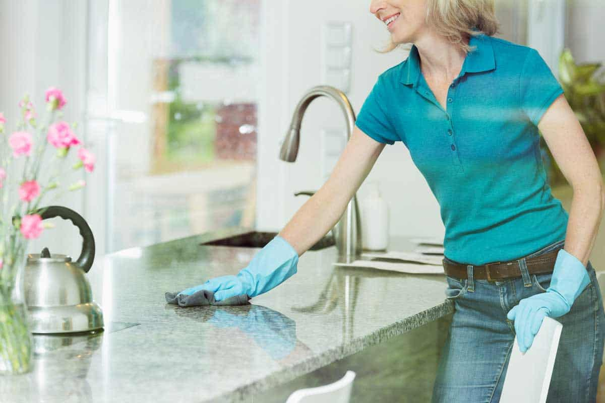 Professional house cleaning service concept, smiling woman wiping down marble kitchen countertop using domestic cleaner, cloth and rubber household gloves, How To Clean Marble Countertops?