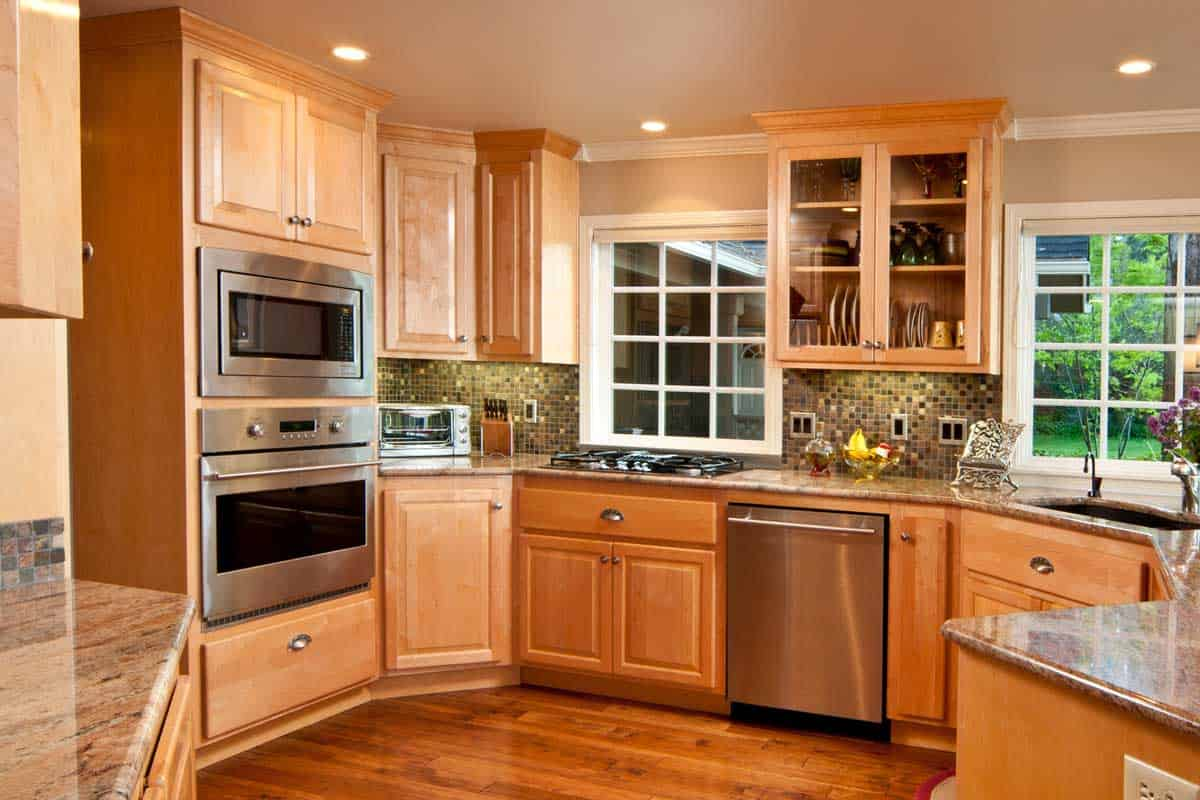 This modern kitchen gives a wide view showing the wood floor and cabinets, How Tall Are Kitchen Cabinets? [3 Types Examined]