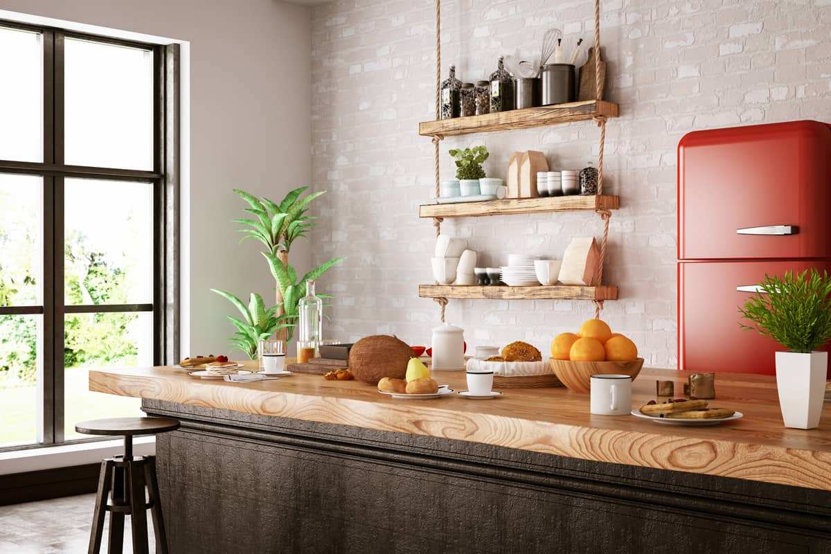 A modern kitchen with a butchers countertop and a hanging spice rack on the wall, How Much Do Butcher Block Countertops Cost? [By size, type, grain and brand]