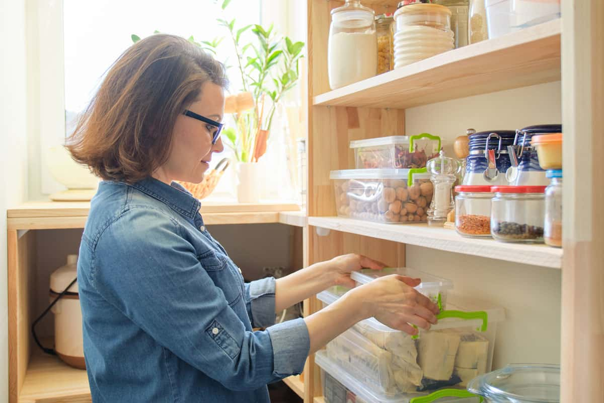 A woman arranging containers on her pantry shelves, 6 Reasons Why You Should Line The Pantry Shelves