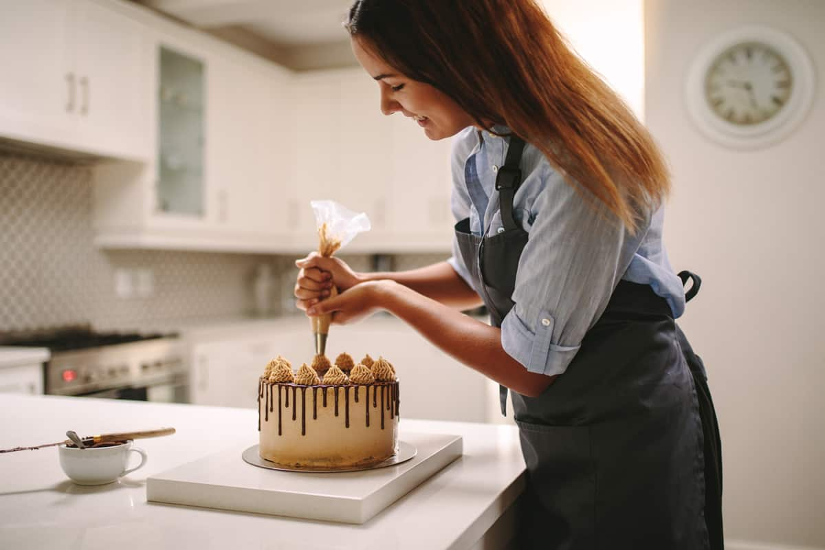 A woman making a fondant cake and putting on frosting using a piping bag, How To Store A Fondant Cake? [5 Easy Solutions]