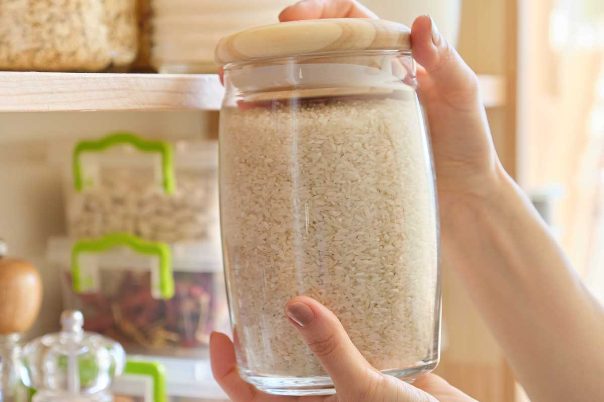 Woman taking a jar of rice in kitchen pantry, Does Rice Go Bad In The Pantry? [Inc. Tips for Keeping Rice Extra Fresh]