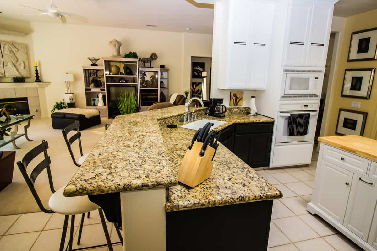 A classic style kitchen with a brown granite countertop and kitchen utensils placed on top, 14 Types of Kitchen Countertops (By Material)