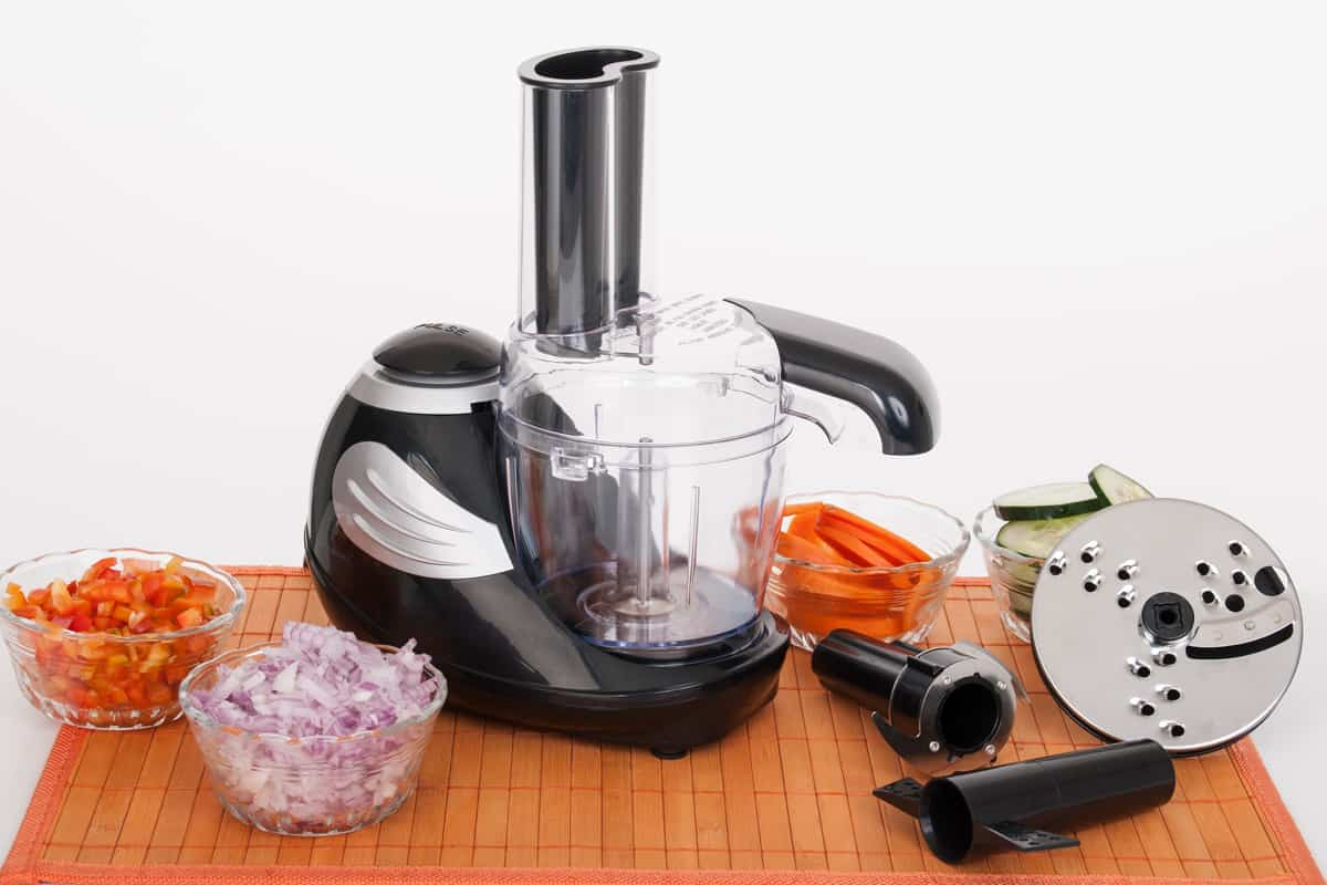 A food processor placed on a chopping board with chopped onions, bell peppers, and carrots on the side, Can You Dice Vegetables In A Food Processor?