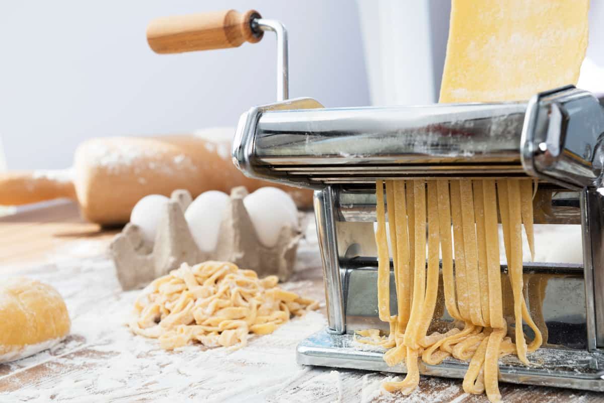 A pasta making machine making pasta with all the needed ingredients on the side, 5 Best Pasta Machine Brands You Should be Looking Into