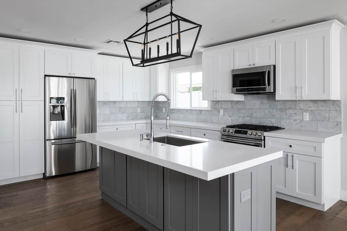 A white and gray themed kitchen with a white granite tiled countertop, Are Kitchen Countertops Glued Down? (And How to Remove Them)