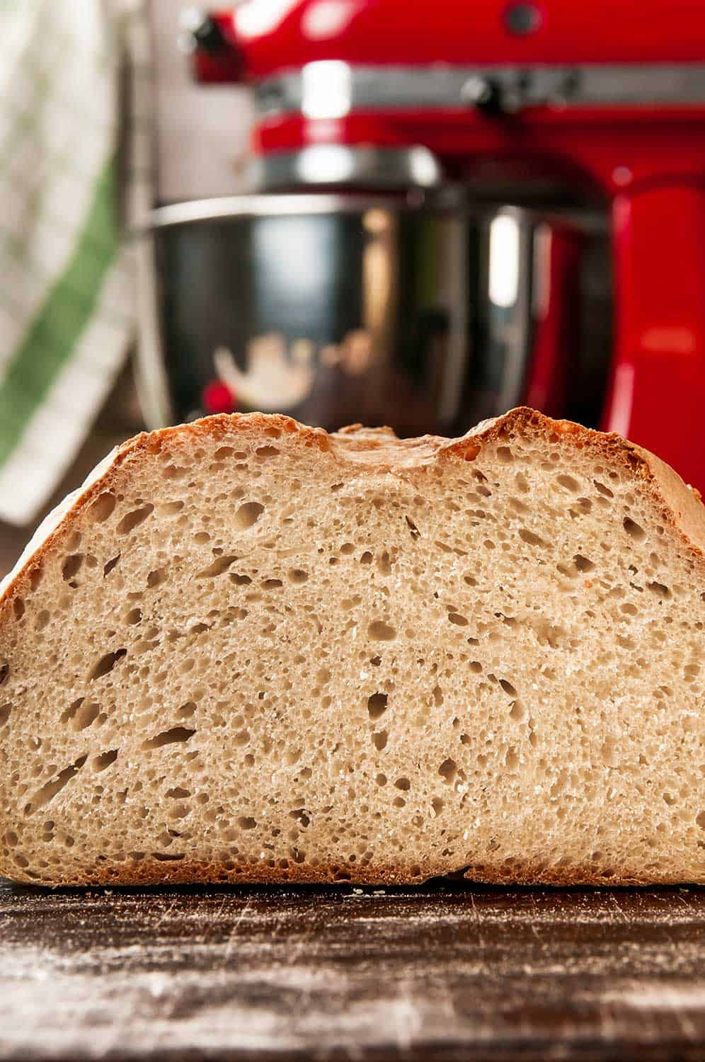 Cross section of home made bread on floured surface and stand mixer on the background