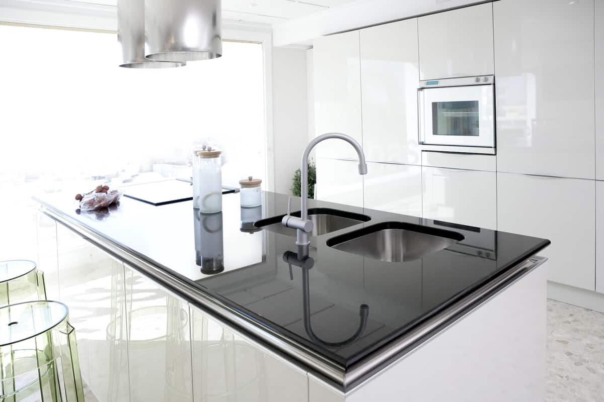 A dark granite colored countertop on a white themed kitchen, How Many Inches Can Granite Hang Without Support?