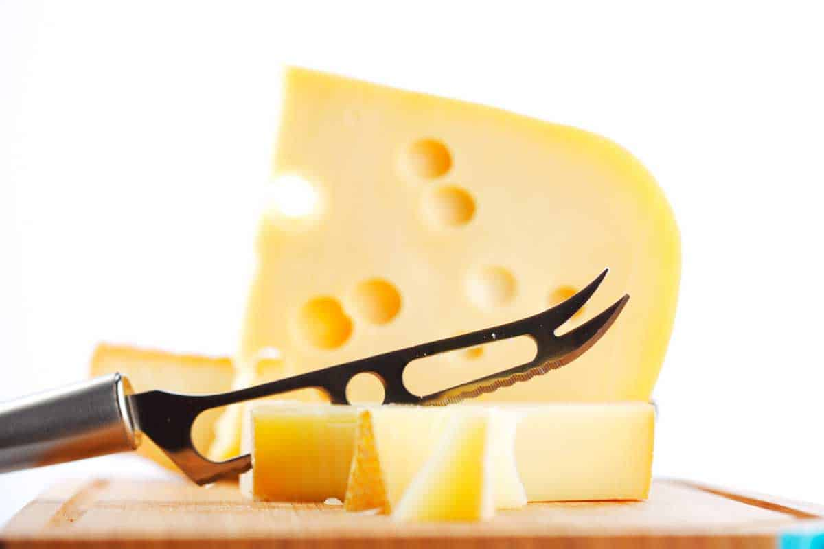Cheese with a cheese knife on a cutting board, What Kind Of Knife Is Best For Cutting Cheese? [6 Options]