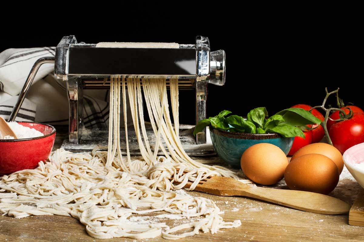 Pasta machine with noodles and ingredients on a wooden table, What Else Can You Use a Pasta Maker For? [9 Awesome Ideas!]