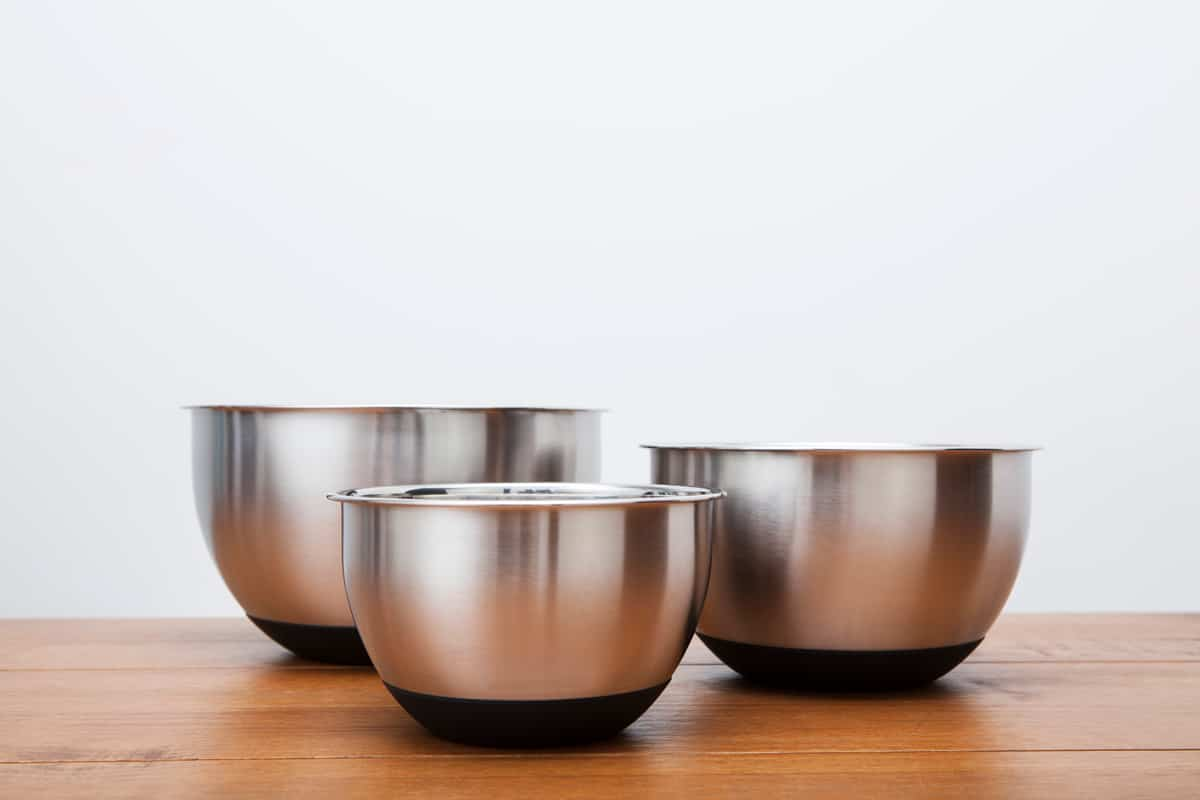 Three different sized mixing bowls on a wooden table, Are Stainless Steel Mixing Bowls Oven-Safe?