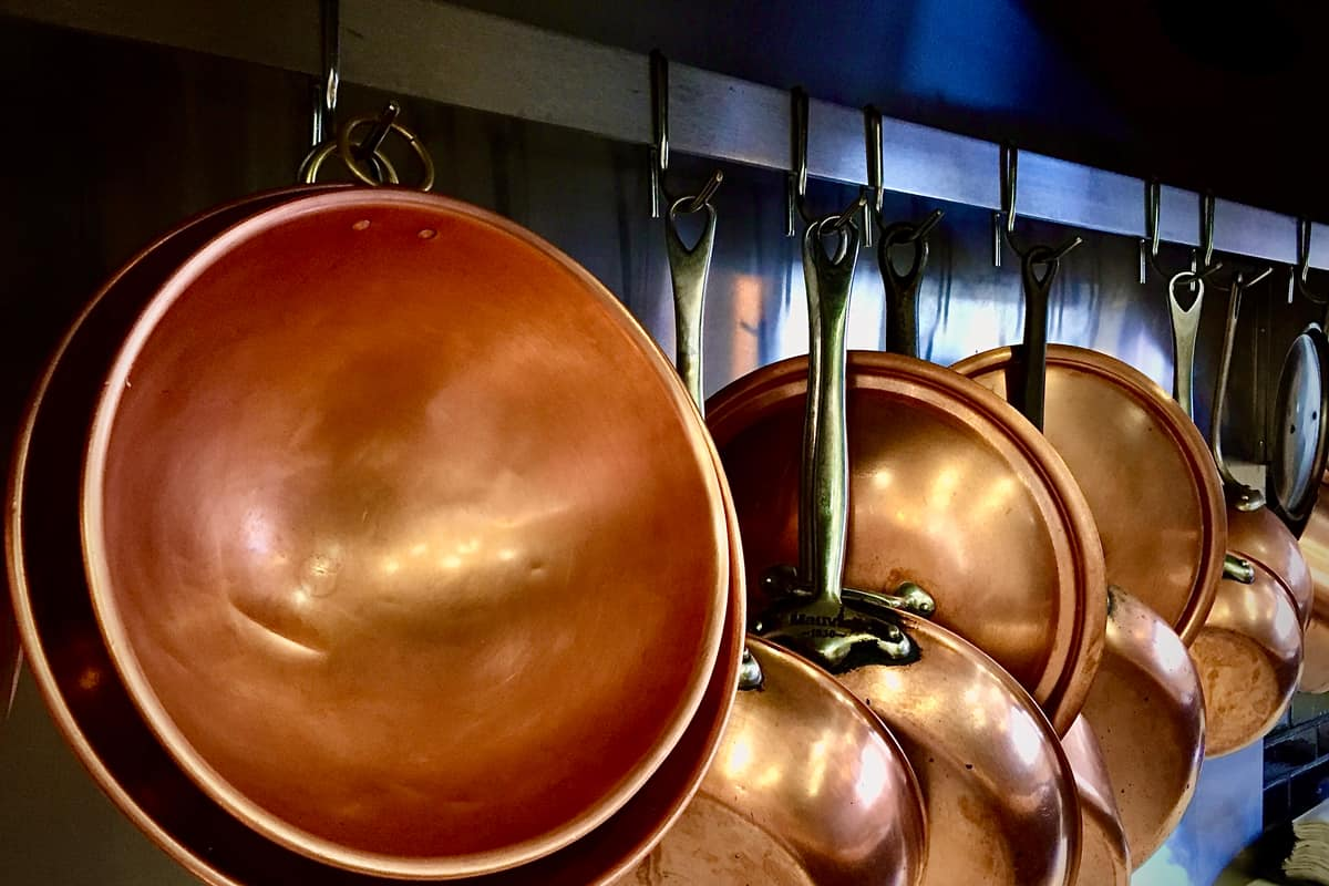 Clean copper sauce pans and mixing bowls hanged on a restaurant wall, How To Clean A Copper Mixing Bowl [4 Effective Ways]