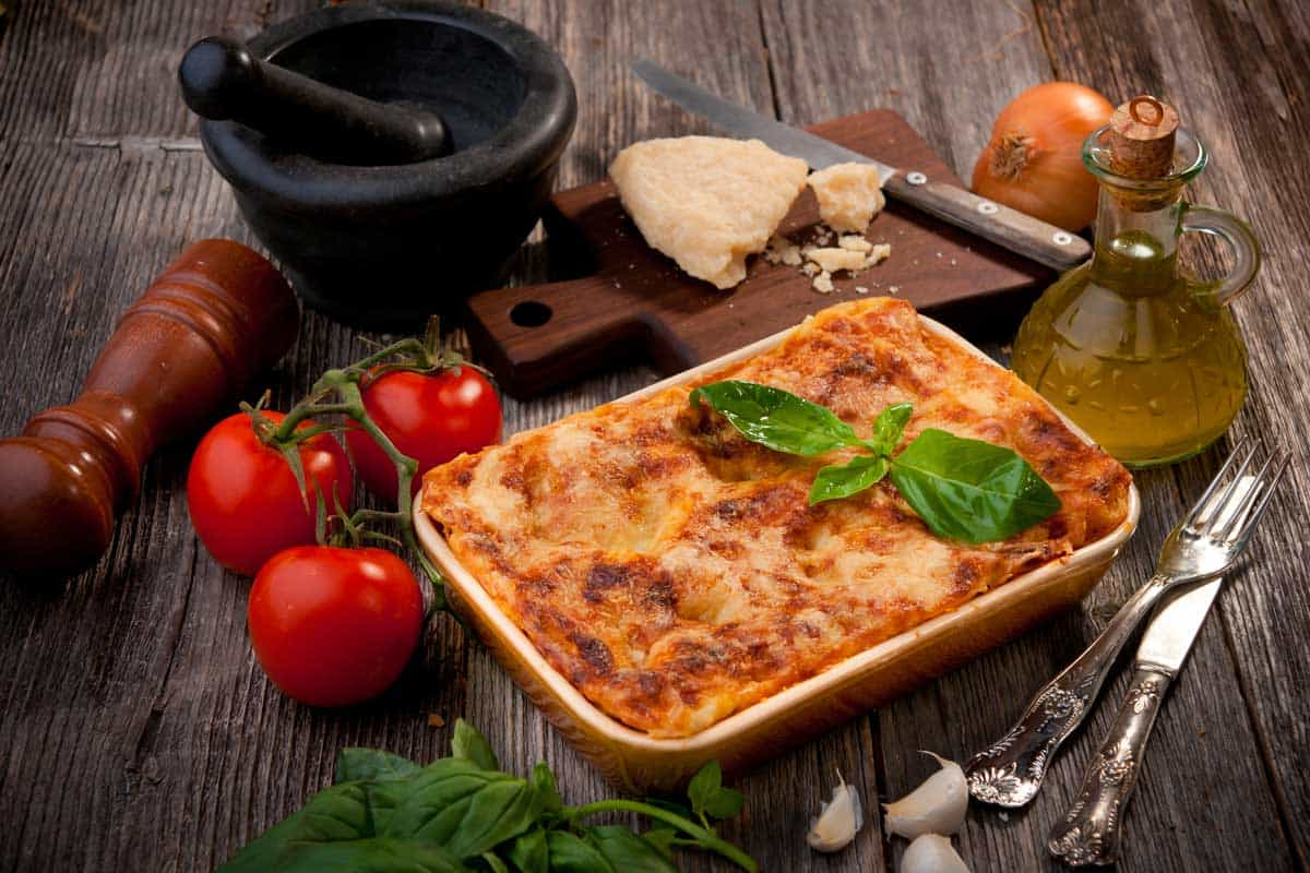 A pan of freshly baked lasagna on a wooden table, Do You Need to Grease a Lasagna Pan?