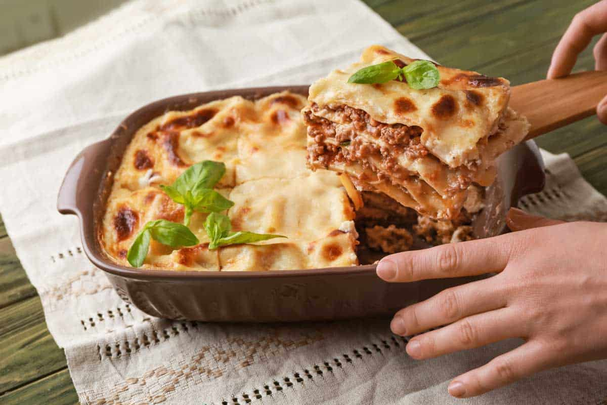 Taking of piece of tasty lasagna from casserole, How Many Layers Should a Lasagna Be? Here's the Answer!