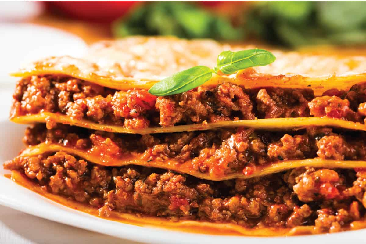 Beef lasagna in a plate with garnish on top, How Much Does It Cost To Make A Pan Of Lasagna