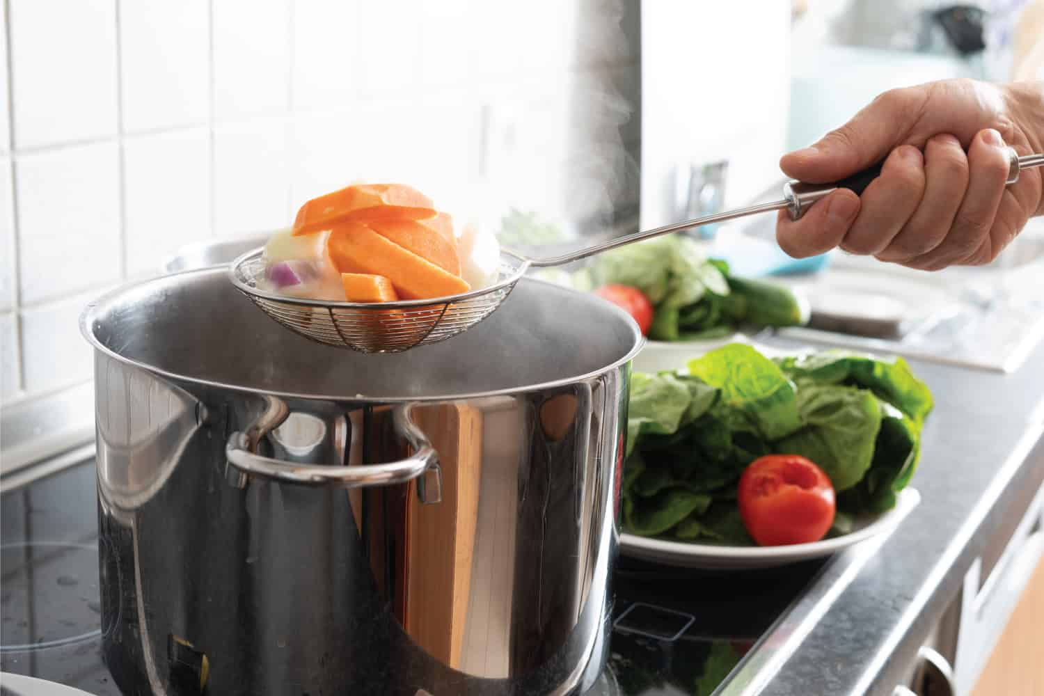 Blanching vegetables in large cooking pot using a strainer
