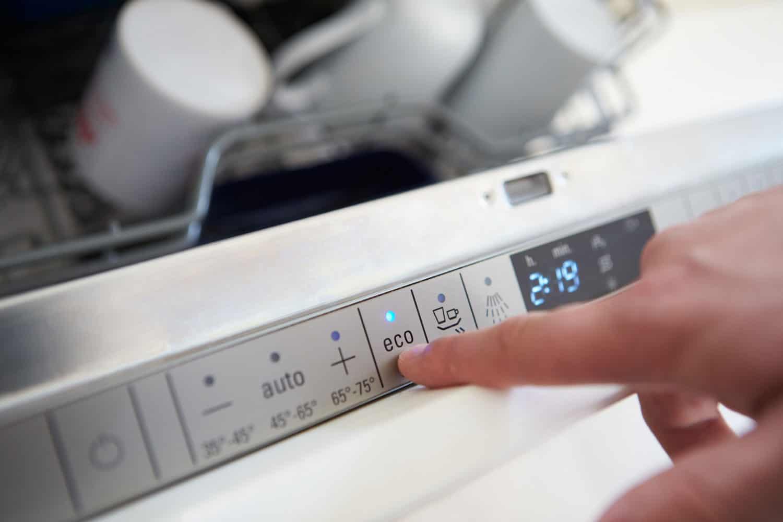 Close Up Of Man Setting Economy Cycle On Dishwasher