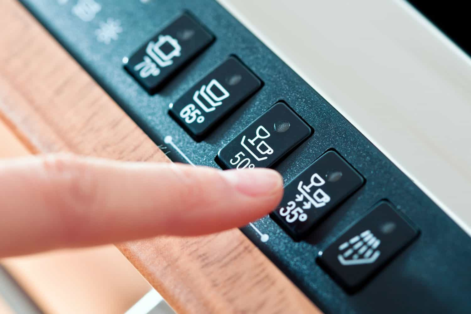 Close-up on woman's finger selecting a program on the panel of dishwasher