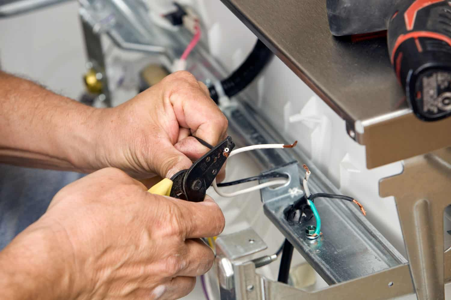 Electrician Strips Wires for a Dishwasher Installation