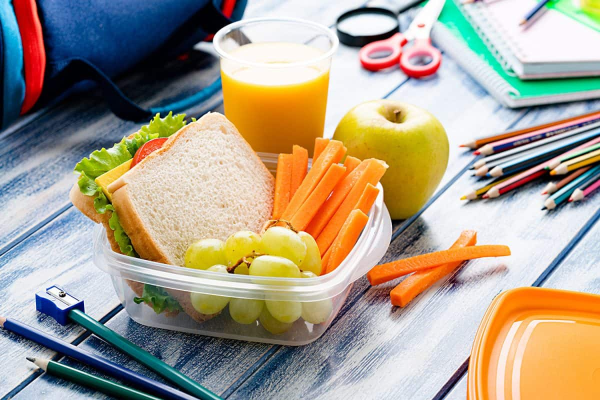 Healthy food for kids concepts: well balanced school lunch box shot on blue table. School supplies are around the lunch box, How To Seal Plastic Food Containers [4 Cool Tricks!]