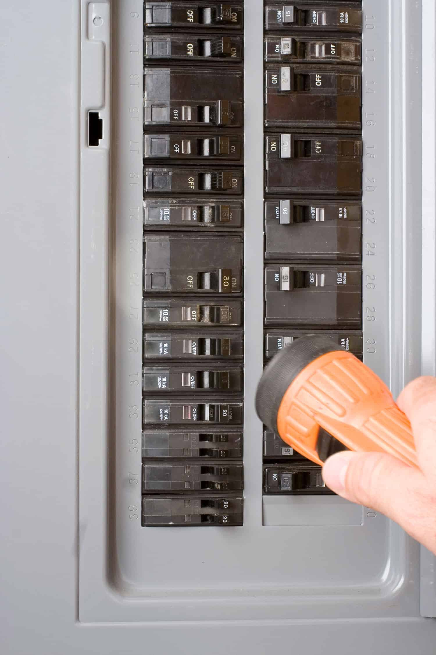 Home electricity power outage. Homeowner uses flashlight to investigate circuit breaker box